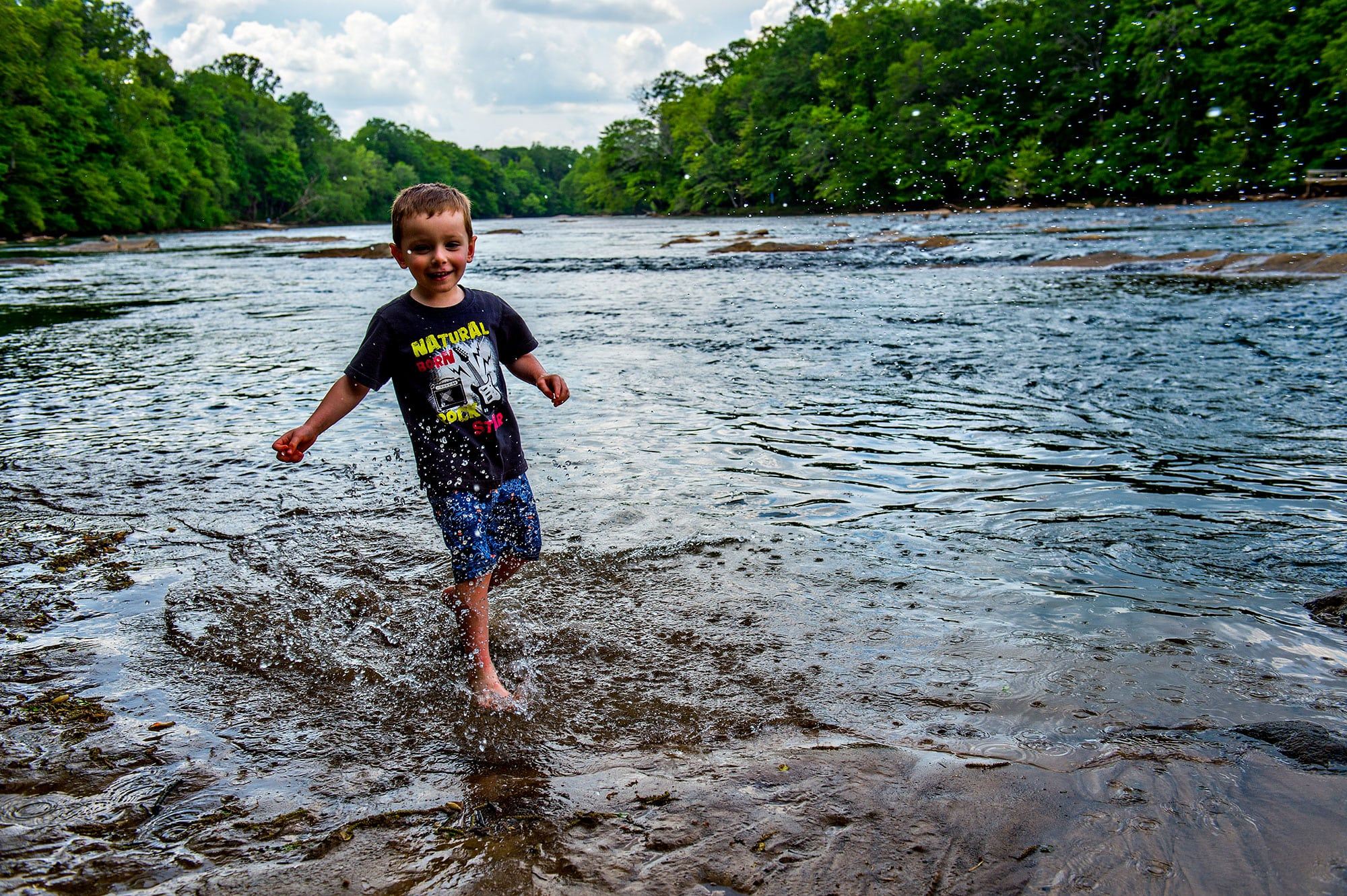 Child wading in the Chattahoochee River in Peachtree Corners, Georgia