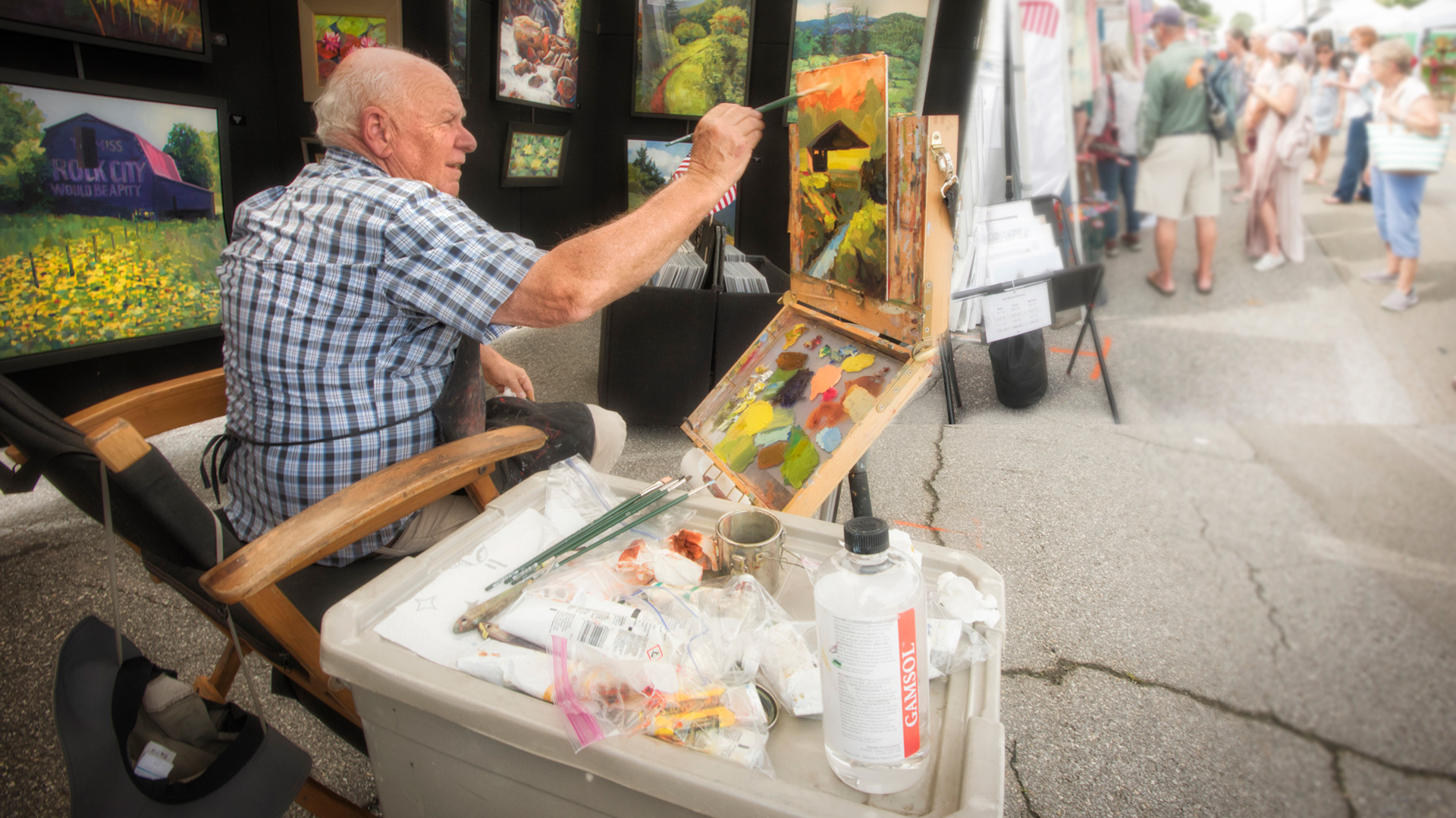 An older gentleman paints in a booth outside at Blue Ridge Arts in the Park.