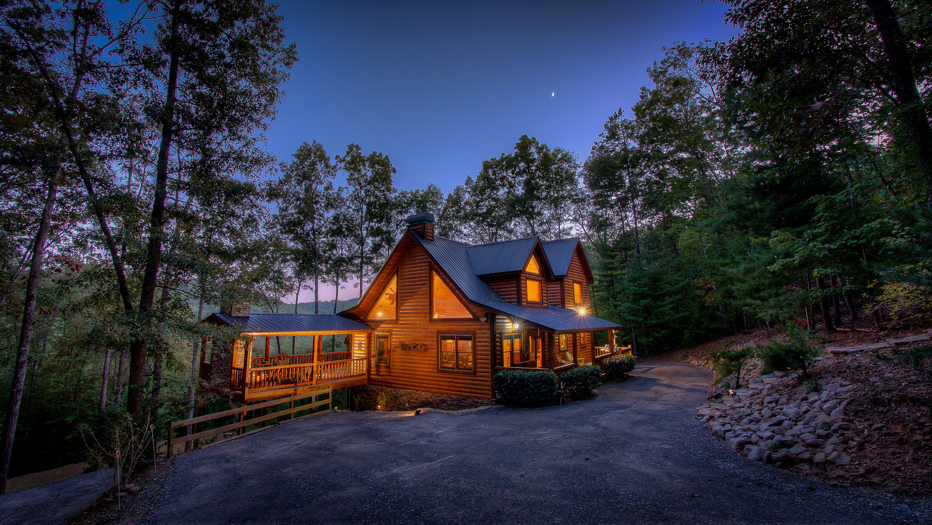 A cozy cabin in Blue Ridge, Georgia, glows warmly among trees and twilight sky.