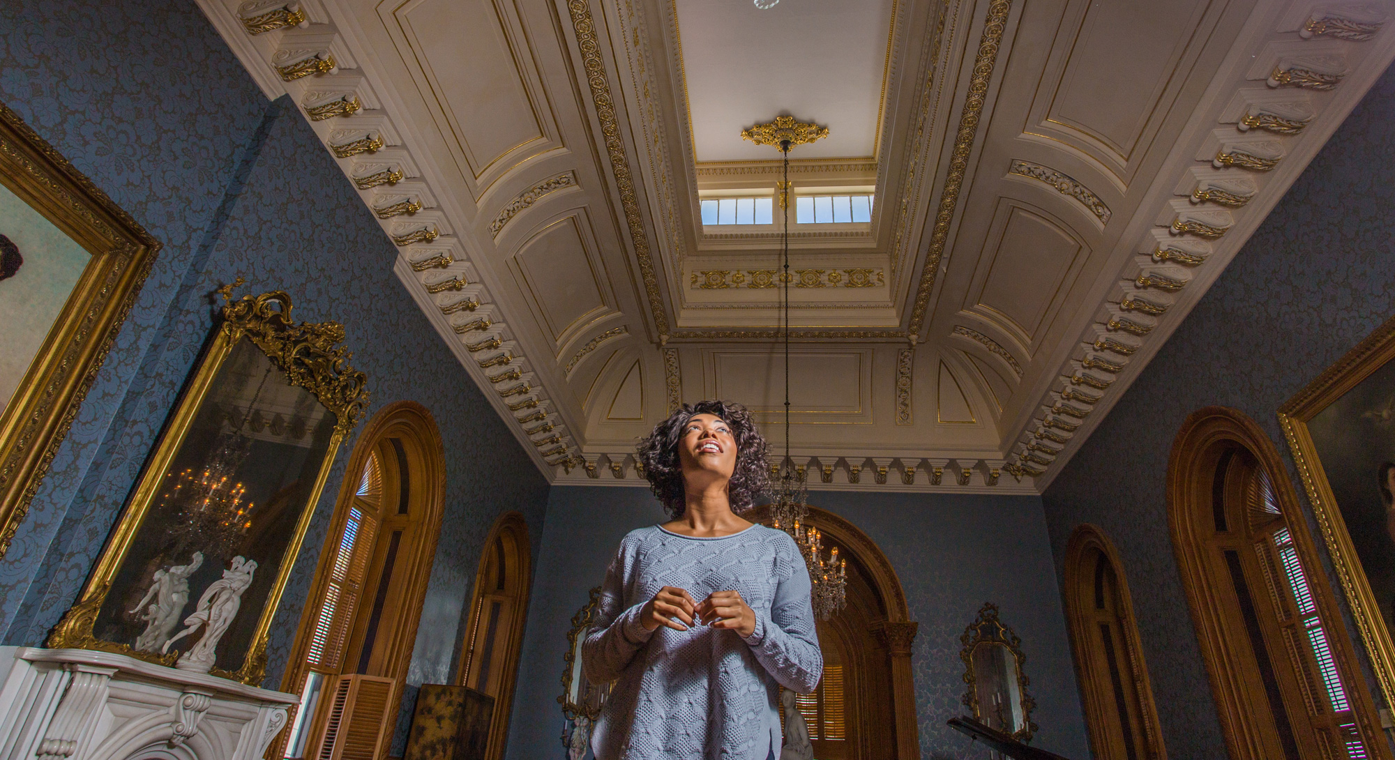 A woman gazes toward the ornate ceiling at the Hay House in Macon, Georgia