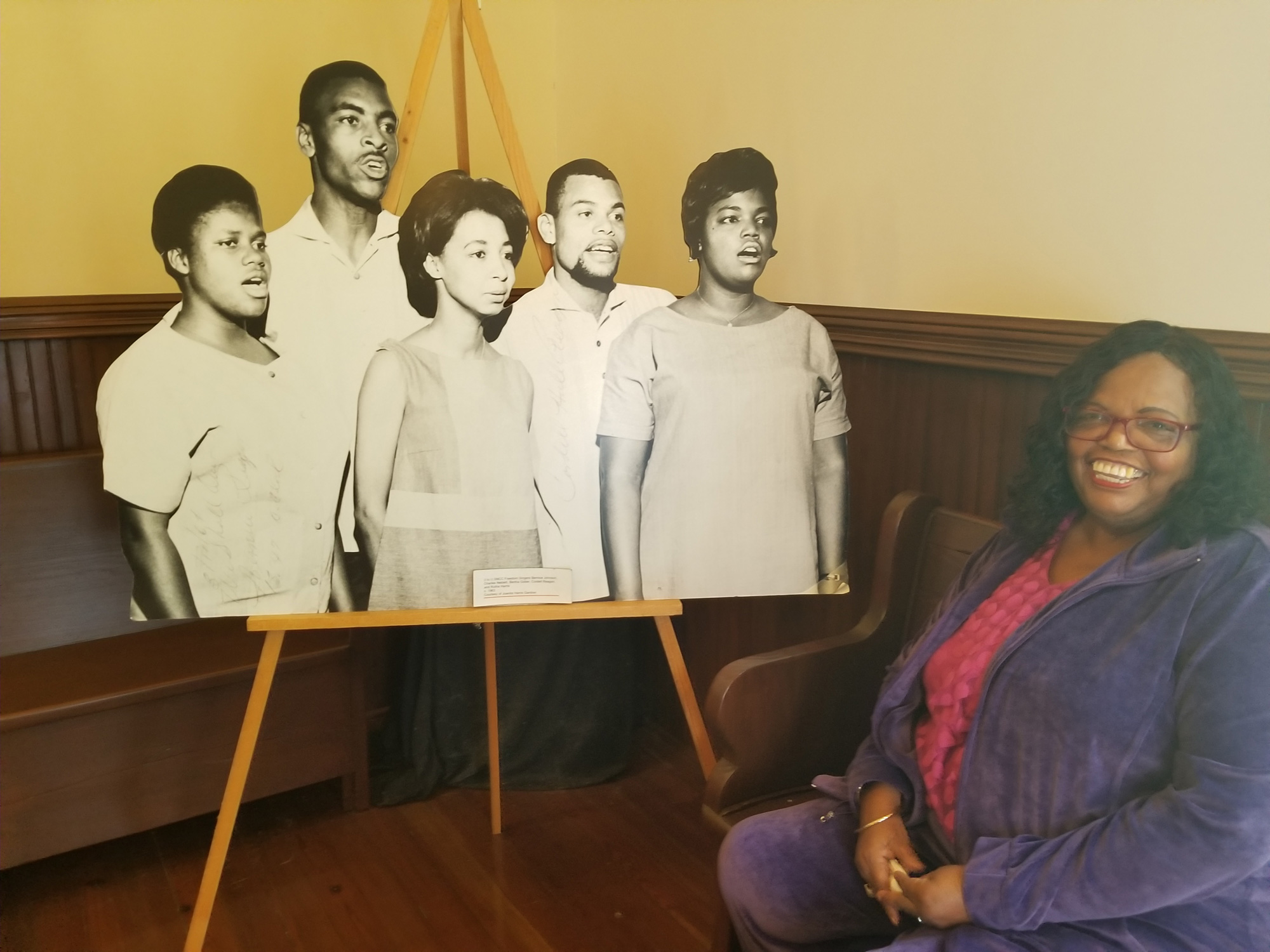 Rutha Harris with a photo of herself and the other original Freedom Singers in the 1960s. Photo by Kalin Thomas