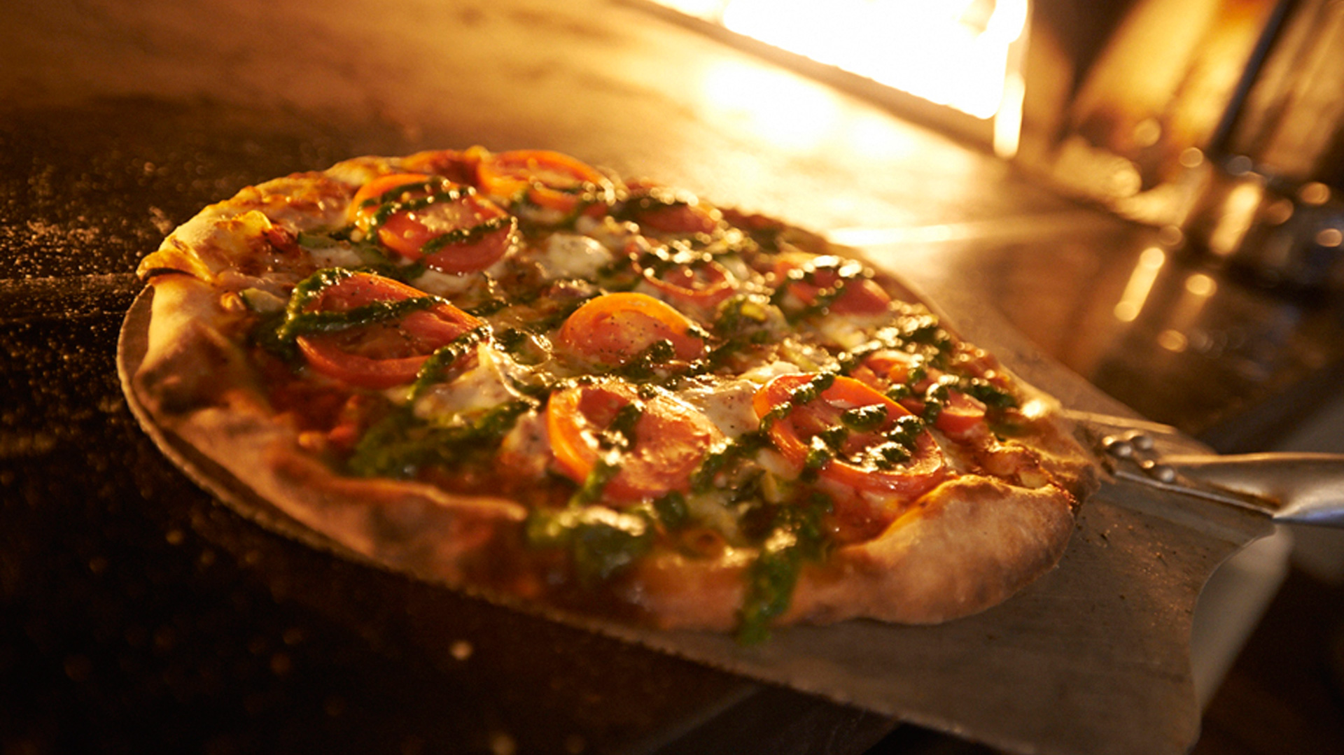 A tomato-topped pizza comes out of the oven at Masseria Kitchen & Bar in Blue Ridge