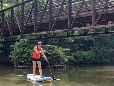 woman in red shirt and red hat paddle boards under a bridge on a lush, green river