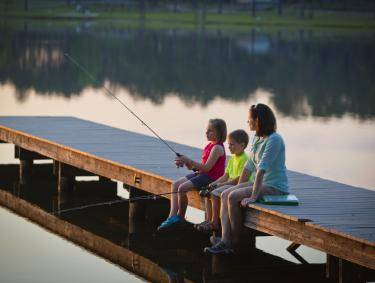 A woman and two children sit on a dock fishing at Seminole State Park in Donalsonville, Georgia