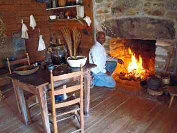 Lawrence Dorsey stokes a fire in the hand-laid rock fireplace and chimney.