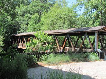 The covered pedestrian bridge is enjoyed by photographers and hikers.