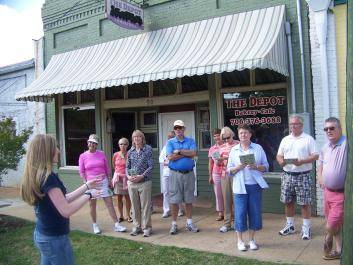 A group learns about the history of Hartwell's Depot Street as part of a guided tour.