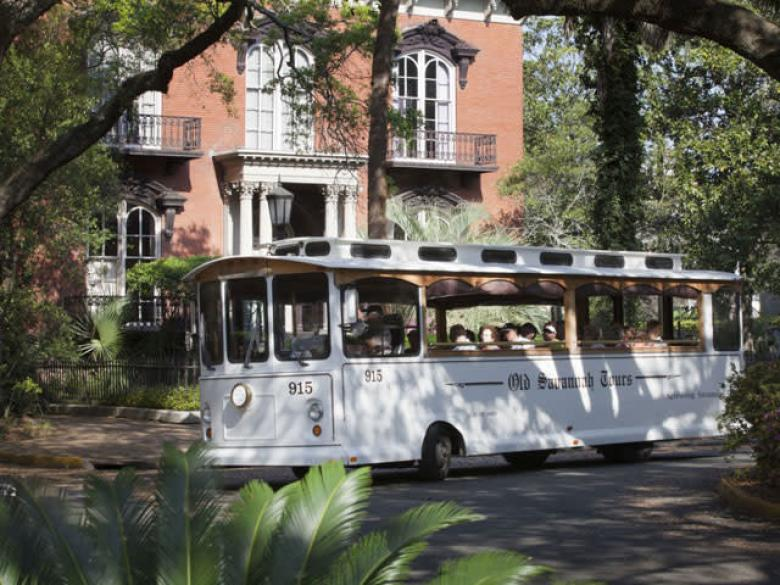 Old Savannah Tours trolley by the Mercer Williams House