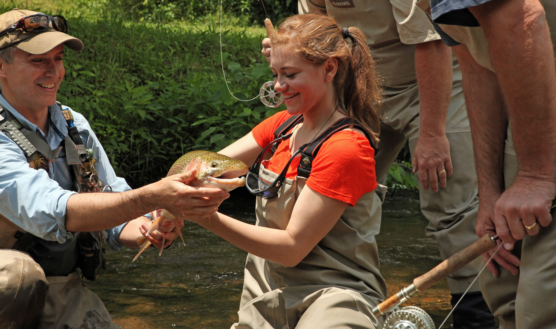 A smiling teenage girl and a fishing guide hold a rainbow trout caught while fishing in Blue Ridge, Georgia